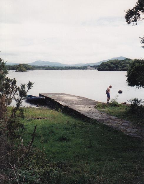 Our little rowboat is on the left of the pier; Ross Castle can be seen in the distance across the lake.